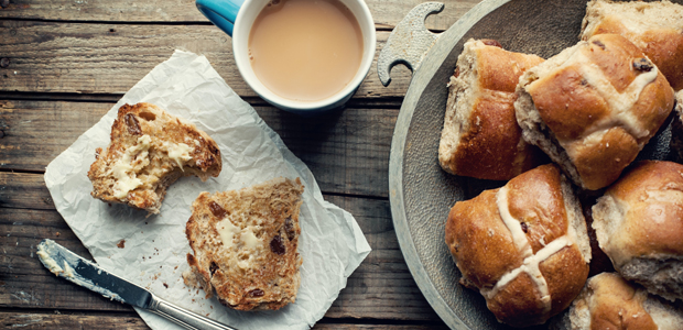 a stack of hot cross buns with butter and a cup of tea
