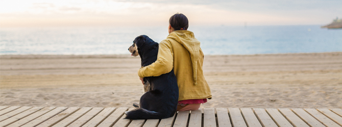 owner and dog gazing out at the ocean